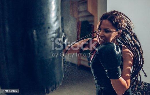 873932790 istock photo Female kickboxer training with a punching bag 873928660