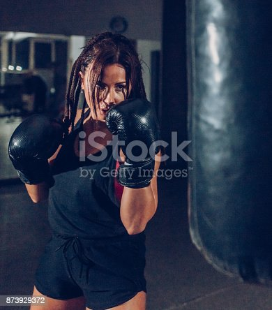 873932790 istock photo Female kickboxer training with a punching bag 873929372