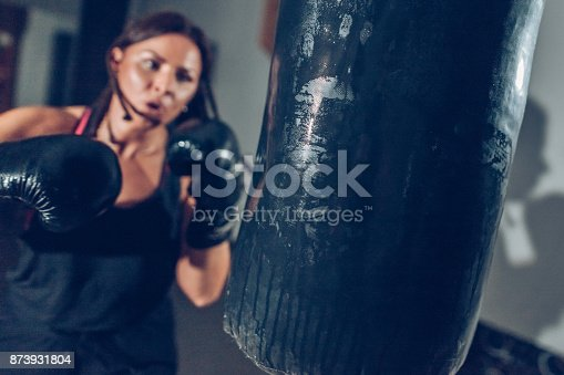 873932790 istock photo Female kickboxer training with a punching bag 873931804