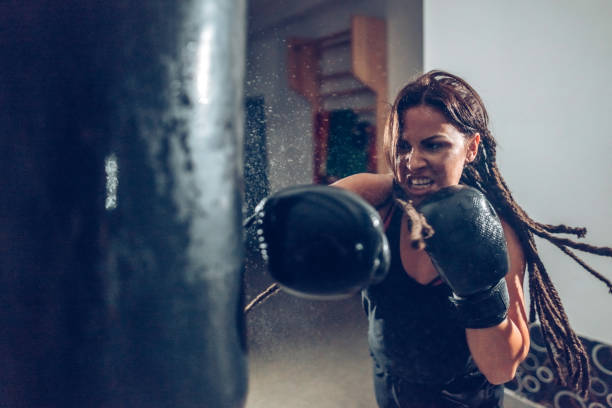 Female kickboxer training with a punching bag Female kickboxer fighter training with a punching bag aggressively stock pictures, royalty-free photos & images