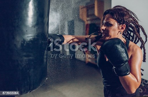 873932790 istock photo Female kickboxer training with a punching bag 873933064