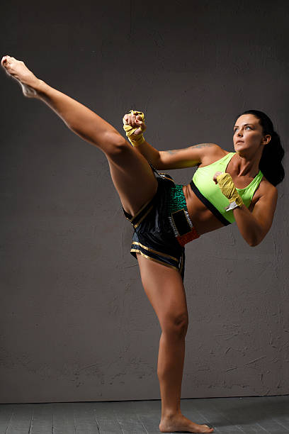 female kickboxing   athletic woman fighter kicking sports training - human limb stock pictures, royalty-free photos & images