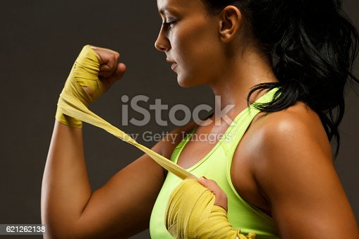 497607484 istock photo Female kickboxing   Athletic woman wrapping hands with yellow boxing wraps 621262138