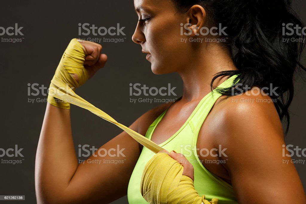 Female kickboxing   Athletic woman wrapping hands with yellow boxing wraps stock photo