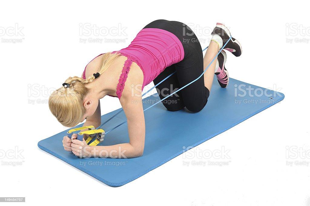Female kneeling butt blaster using rubber resistance band royalty-free stock photo