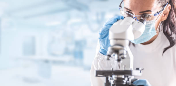 Female lab technician in protective glasses, gloves and face mask sits next to a microscope in laboratory. stock photo