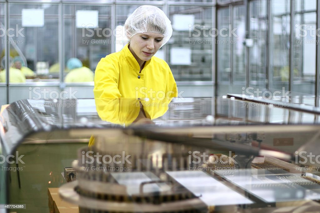 Female lab technician wearing hair net and yellow jumpsuit stock photo