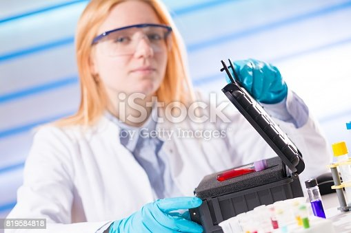 646435702istockphoto Female laboratory assistant with blood test for AIDS 819584818