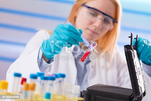 646435702istockphoto Female laboratory assistant with blood test for AIDS 819584846
