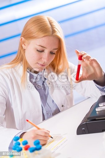 646435702istockphoto Female laboratory assistant with blood test for AIDS 819584864