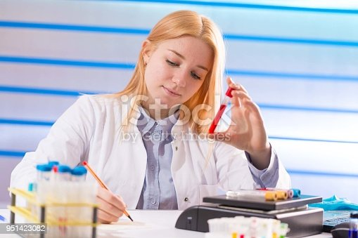 646435702istockphoto Female laboratory assistant with blood test for AIDS 951423082