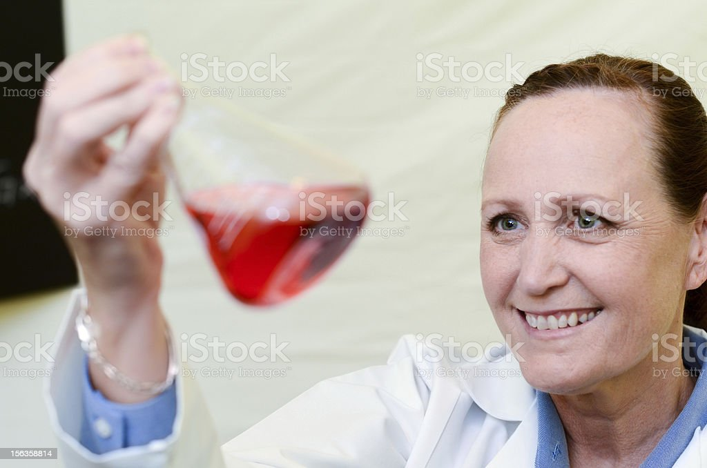 Female laboratory technician inspects red liquid in a beaker royalty-free stock photo