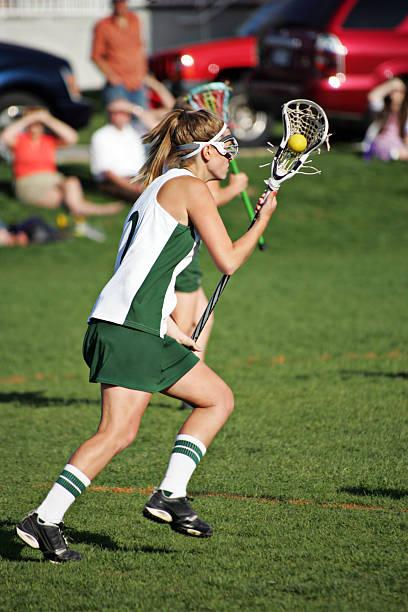 kobieta lacrosse player w zielone i białe biegu z piłką - lacrosse zdjęcia i obrazy z banku zdjęć
