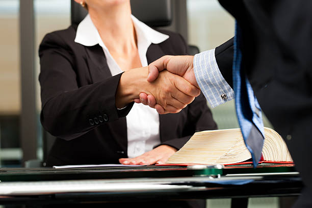 Female Lawyer or notary in her office Mature female lawyer or notary with client in her office - handshake jurist stock pictures, royalty-free photos & images