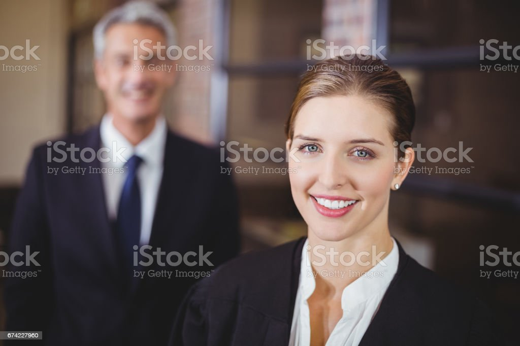 Female lawyer smiling while male colleague in background stock photo