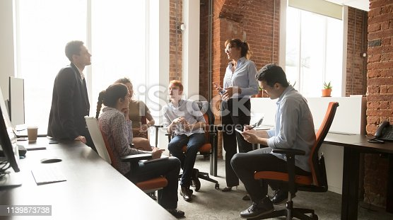 Female leader coach mentor teacher talking to sales team at diverse group office stand up meeting consulting employees, mentor teaching interns, businesswoman manager speaking at corporate training