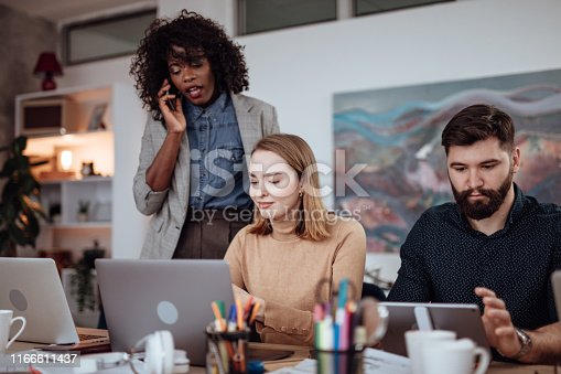 Female leader supervise her employees while talking on the phone