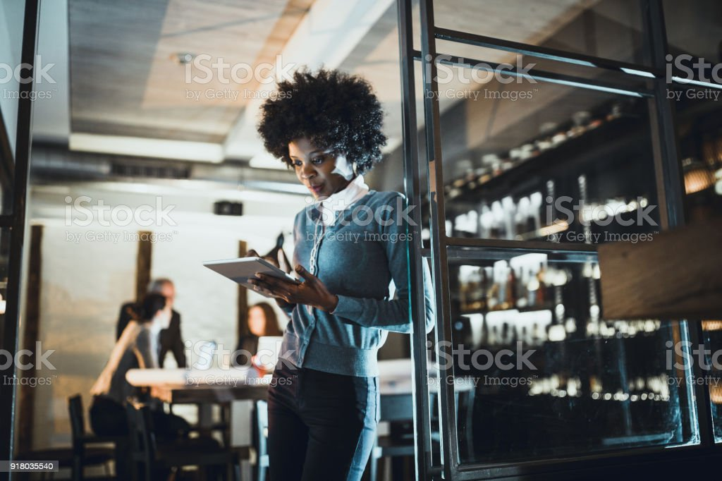 Female Leaders. Young African-American woman, architect working late in office stock photo
