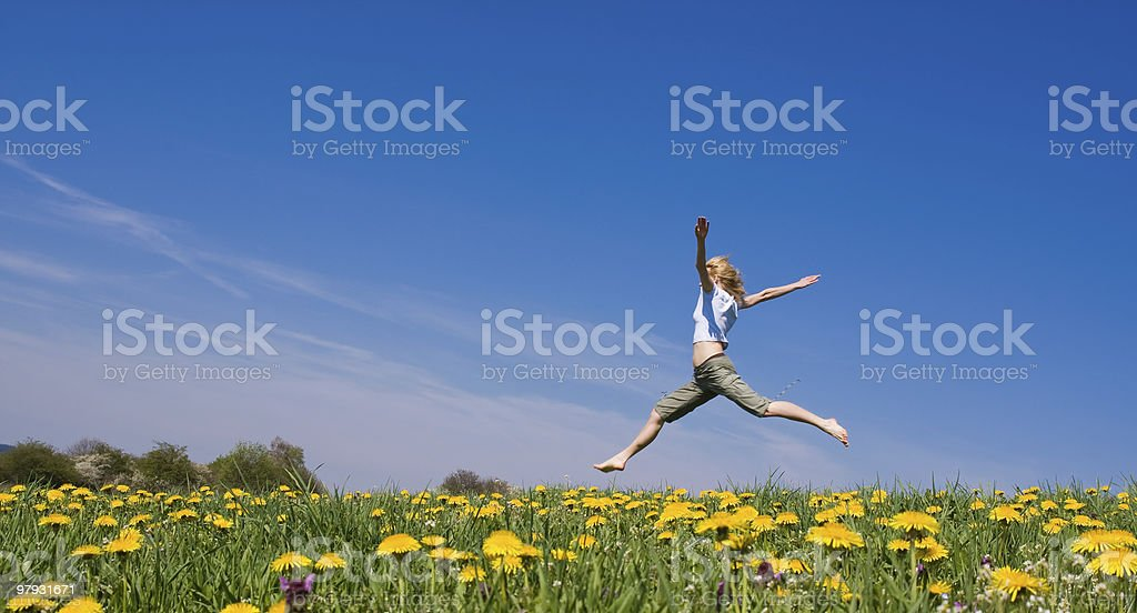 Female leaping through a spring meadow royalty-free stock photo