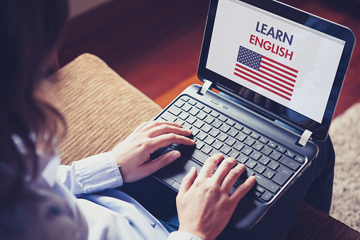Woman sitting at home with a laptop on the knees and a website to learn American English on the screen.