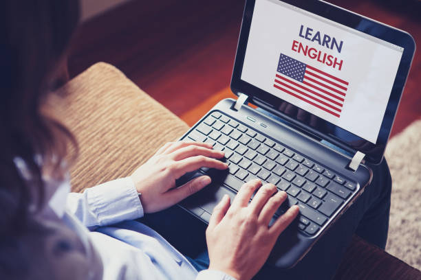 Female learning english at home with a laptop. Woman sitting at home with a laptop on the knees and a website to learn American English on the screen. english language stock pictures, royalty-free photos & images