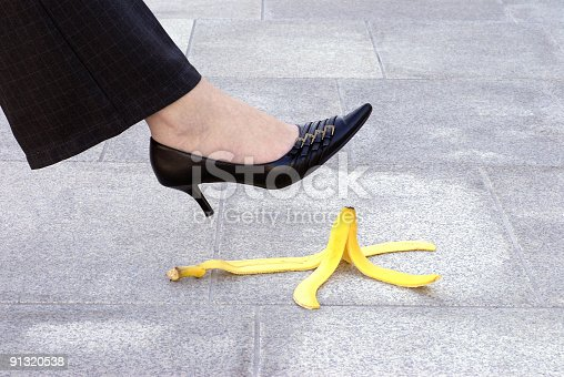 Female executive or businesswoman about to step on a banana skin.  Alternative version shown below: