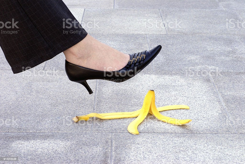 Female leg about to step on banana skin stock photo