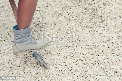 istock Female leg diggings stone for the cement with shovel. Close-up. Concept 947408386