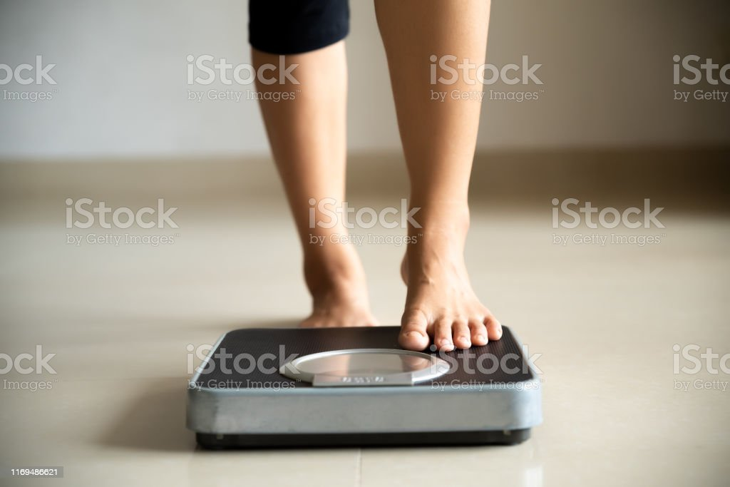Female leg stepping on weigh scales. Healthy lifestyle, food and sport concept. - Foto stock royalty-free di Accudire
