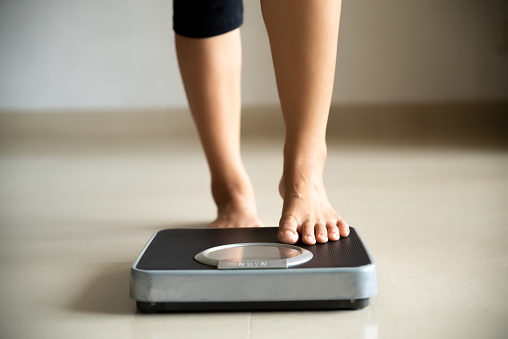 Female Leg Stepping On Weigh Scales Healthy Lifestyle Food And Sport Concept - Fotografie stock e altre immagini di Accudire