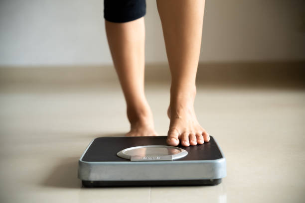 Female leg stepping on weigh scales. Healthy lifestyle, food and sport concept. Female leg stepping on weigh scales. Healthy lifestyle, food and sport concept. and stock pictures, royalty-free photos & images