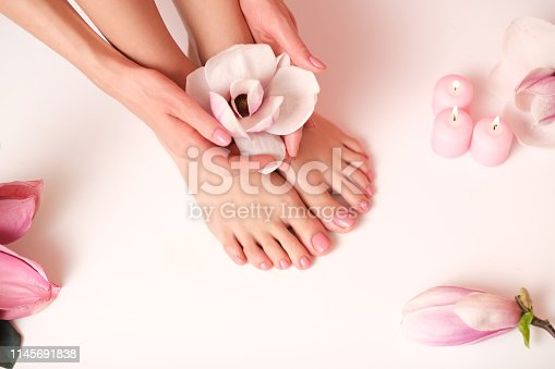 938027870 istock photo Female legs and hands surrounded by flower flakes. 1145691838