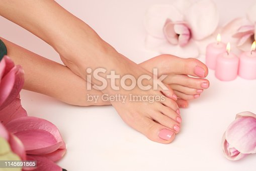 938027870 istock photo Female legs and hands surrounded by flower flakes. 1145691865