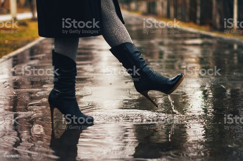 Female legs and women leather boots in the rain stock photo