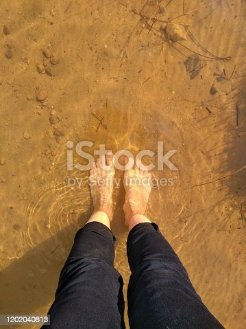 Female legs barefoot in the water lake top view background relaxing on a nature