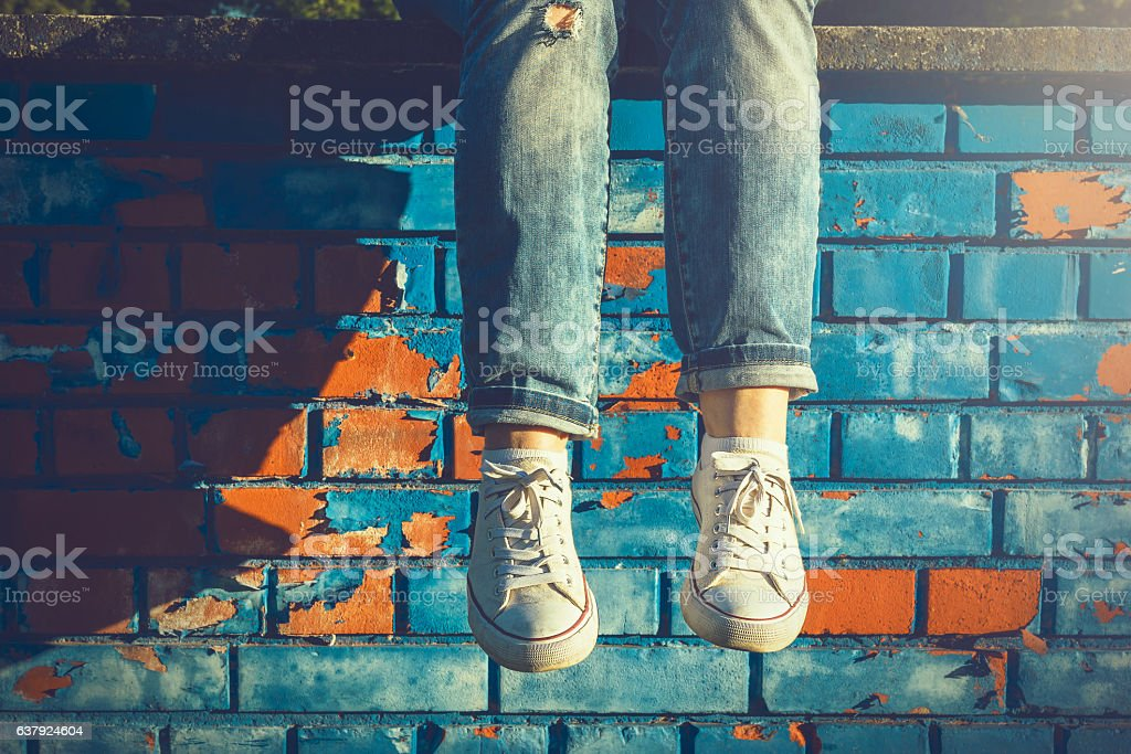Female legs dangling from a blue brick wall stock photo