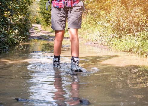 istock female legs, hiking boots pass swamp 1066554740