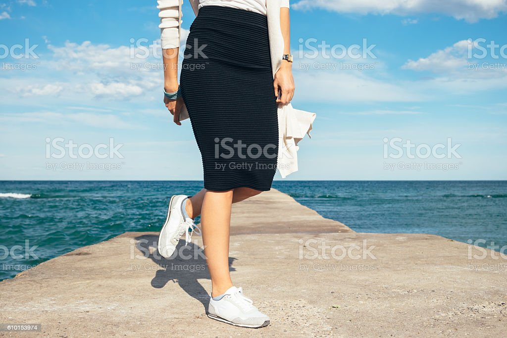 Female legs in a skirt and sneakers stock photo