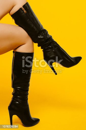 Female legs in black high-heeled boots isolated on yellow background.