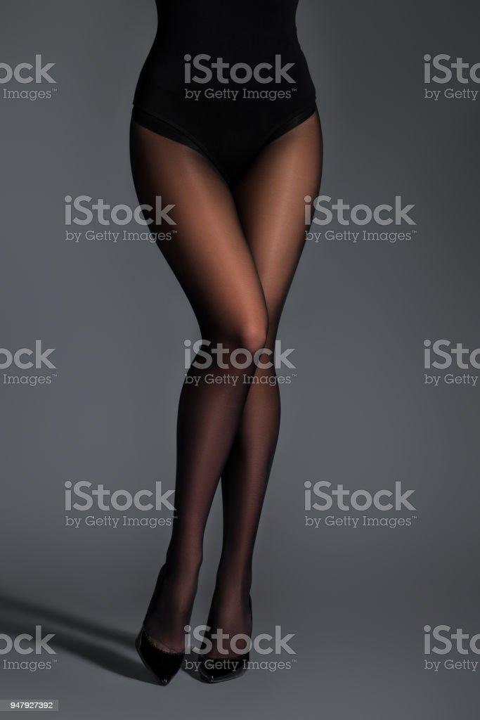 Weibliche Beine In Schwarzen Strumpfhosen Auf Dunklem