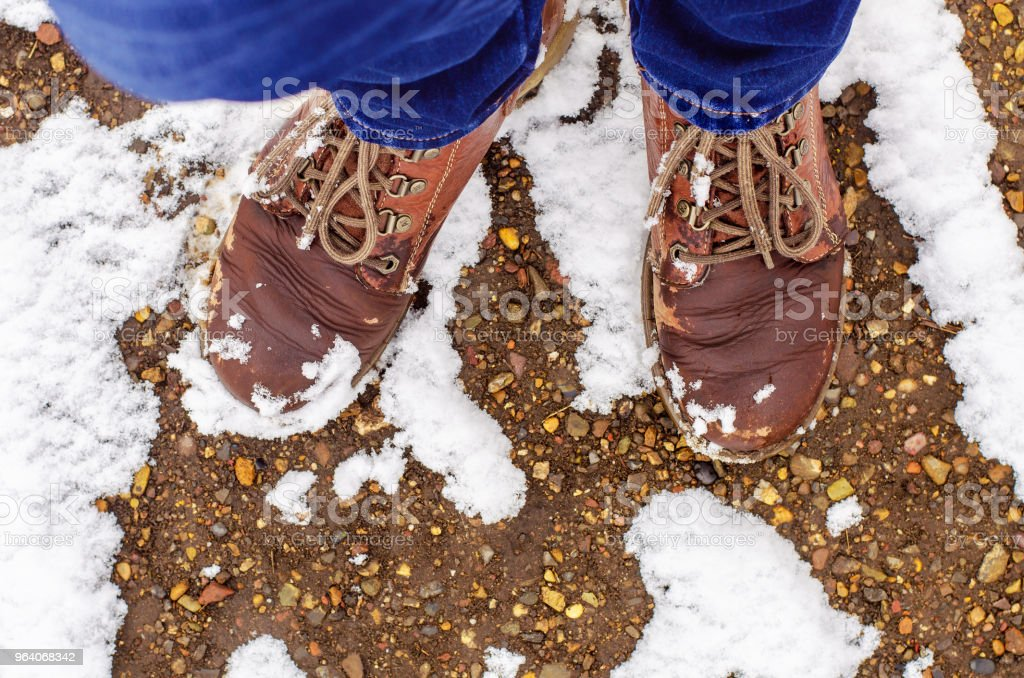 female legs in blue jeans and old brown leather boots stand on a slightly snow-covered stone path - Royalty-free Blue Stock Photo