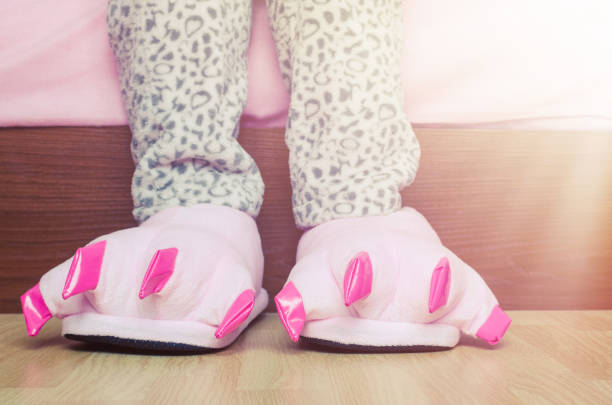 female legs in cute pink monster foot slippers - pajamas stock photos and pictures