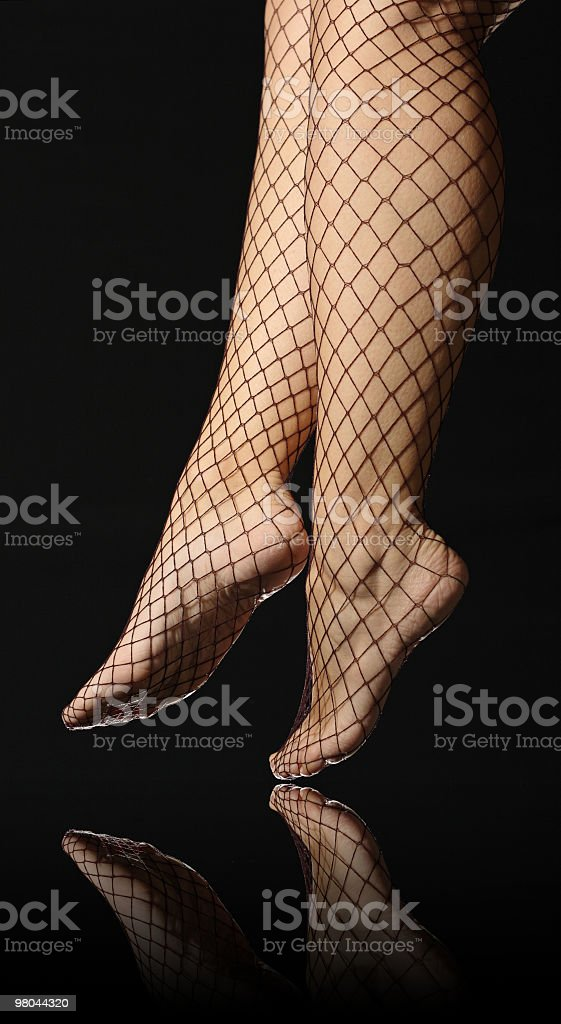 Female legs in fishnet stockings royalty-free stock photo