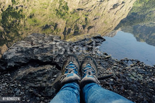Female legs in jeans and hiking boots near edge of mountain lake. Rocks reflection on water surface