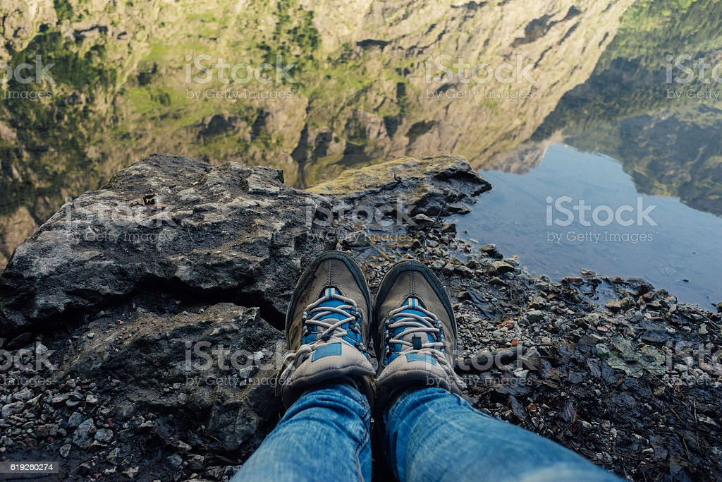 Female legs in jeans and hiking boots against mountain lake stock photo