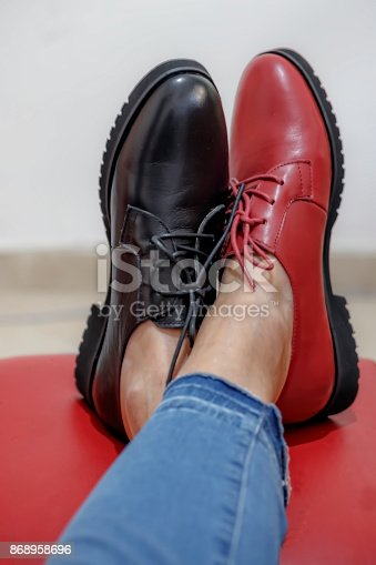 Part of the female legs in jeans are shod in different color shoes on a red stool