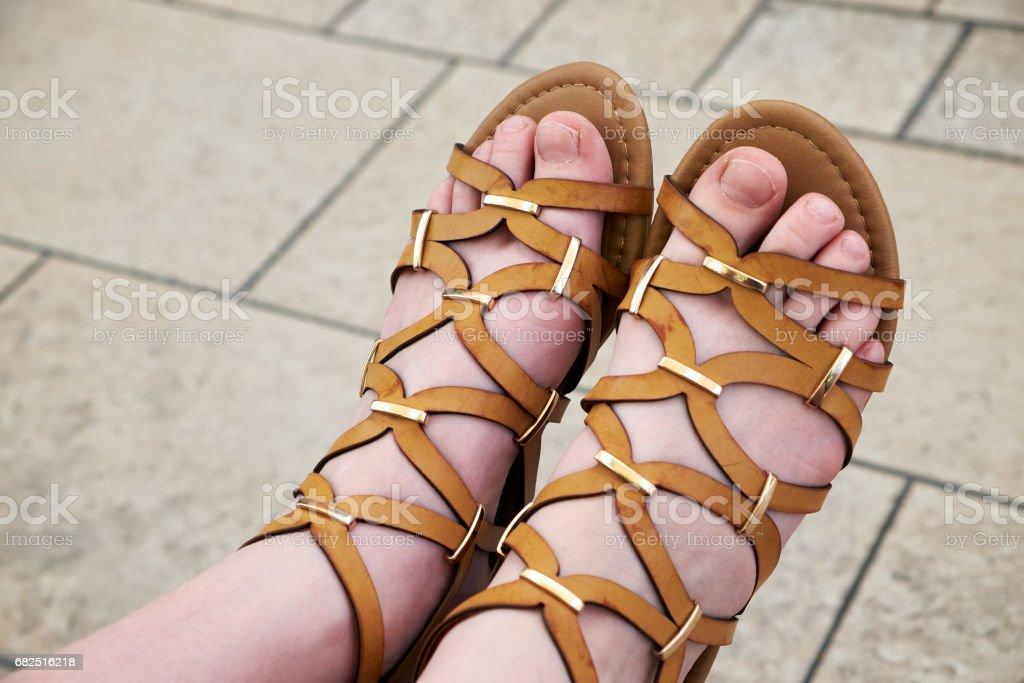 Female legs in sandals in the sunlight. Lizenzfreies stock-foto