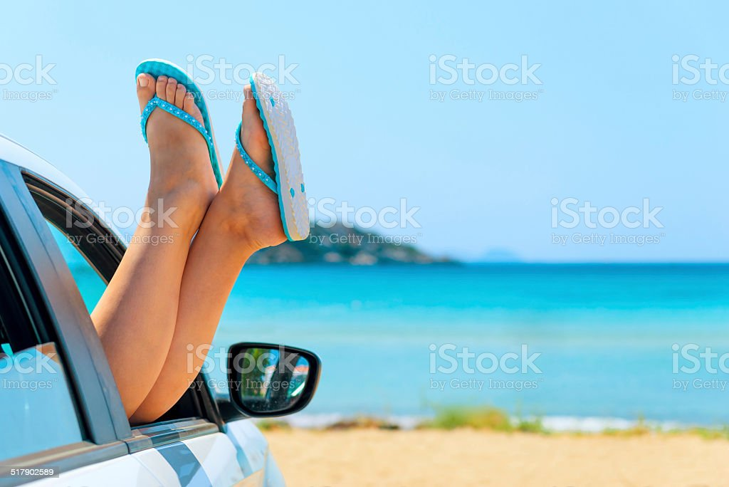 female legs in shales on sea background stock photo