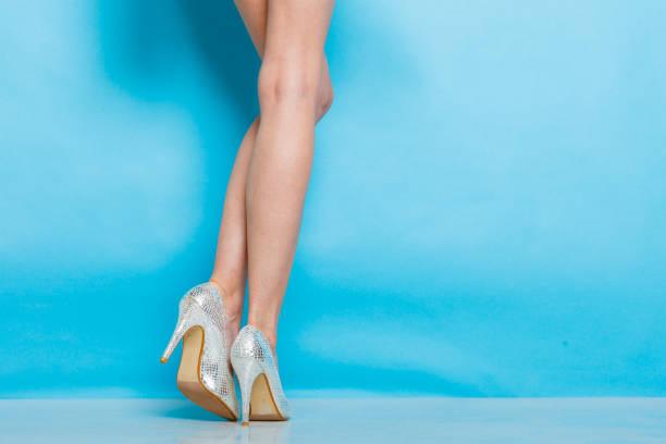 weibliche beine in silbernen high heels schuhe - glitzer absätze stock-fotos und bilder