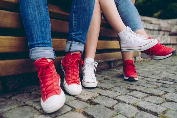 weibliche beine in turnschuhen - sitzbank schuhe stock-fotos und bilder